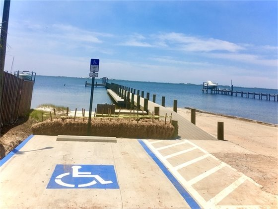 Photo of Woodlawn Beach Boat Ramp showing new handicap accessible parking space and newly rebuilt pier with water in the background