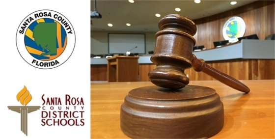Gavel in commissioner boardroom with School & BOCC Logo