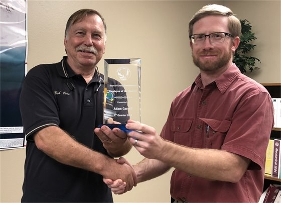 Commission Chairman Bob Cole presents Adam Carroll with the Employee of the Quarter award