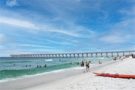 Photo of Navarre Beach showing people swimming in the ocean with a pier in the background