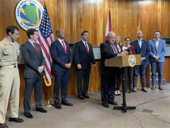 Commission Chairman Dave Piech speaks at Governor Ron DeSantis' press conference in Milton