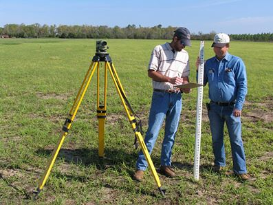 Picture of two people taking a survey of a field
