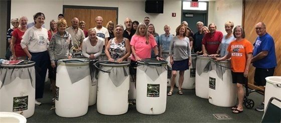 Participants from last rain barrel workshop shown with completed rain barrels